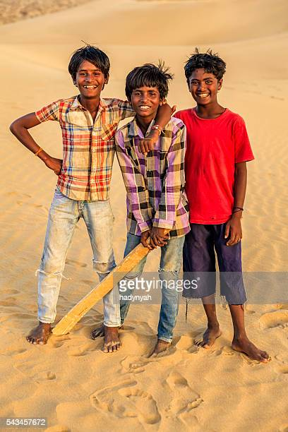Young Indian boys playing cricket on sand dunes, India