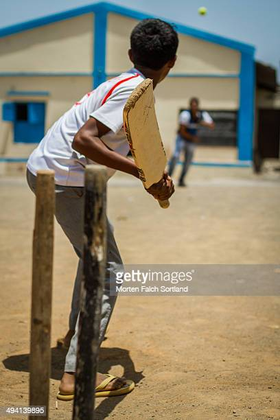 Young Indian boys playing cricket outside a building by the port in Daman, Gujarat. The oldest boy is throwing the ball towards the camera, and the...