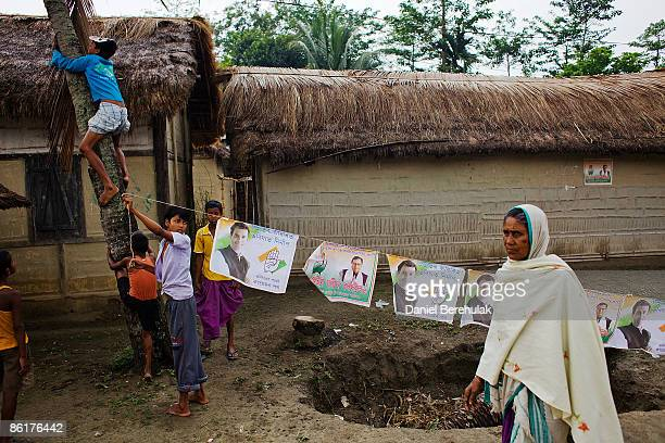 Young Indian boys put up Congress Party flags displaying candidate Rahul Gandhi near a polling station on April 23 2009 in the Muslim dominated town...