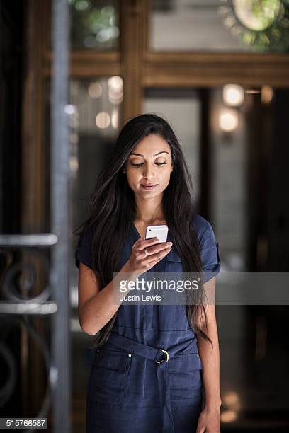 Young indian business woman looking at phone