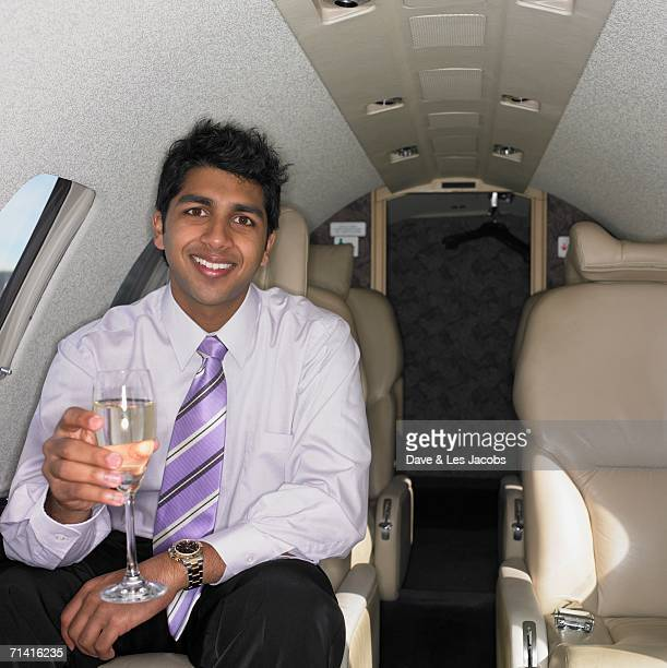 Young Indian businessman drinking inside airplane