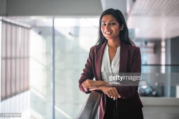young indian businesswoman looking at camera and smiling - businesswoman stock pictures, royalty-free photos & images