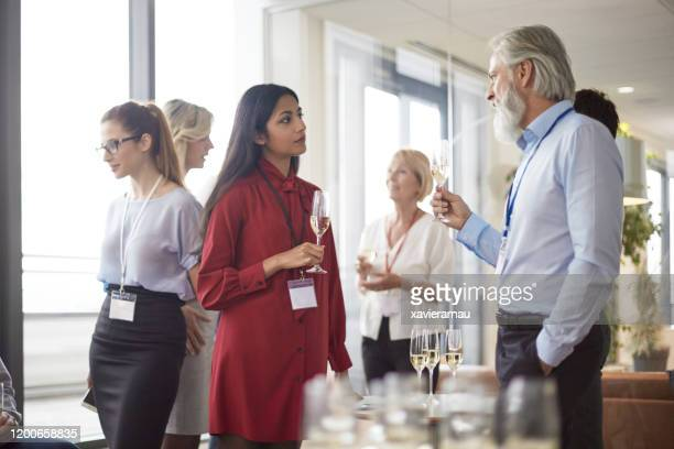 young indian businesswoman talking with ceo at party - publicity event stock pictures, royalty-free photos & images