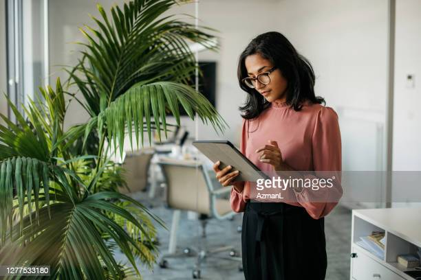 young indian businesswoman using digital tablet in office - businesswoman stock pictures, royalty-free photos & images