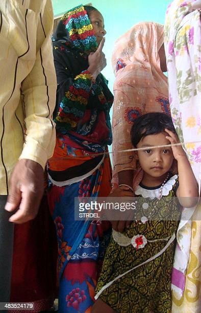 A young Indian child holds onto her mother's hand as they queue with others at a polling station in Lalpani in the northeastern state of Manipur on...