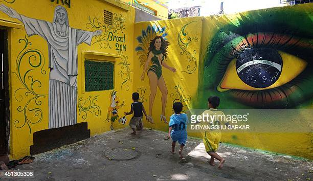Young Indian children in Brazil and Argentina football attire play in front of wall graffiti supporting their favorite team Brazil in Kolkata on June...