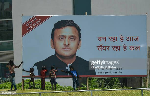 Young Indian children play around a hoarding featuring an image of Uttar Pradesh Chief Minister Akhilesh Yadav in Greater Noida on April 12 2016 /...