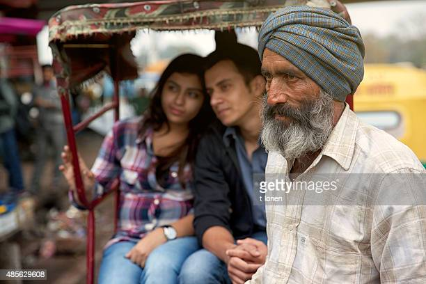 Young indian couple in rickshaw w their driver.