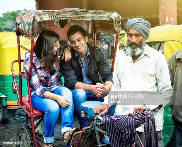 young indian couple in rickshaw w their driver. - rickshaw stock photos and pictures