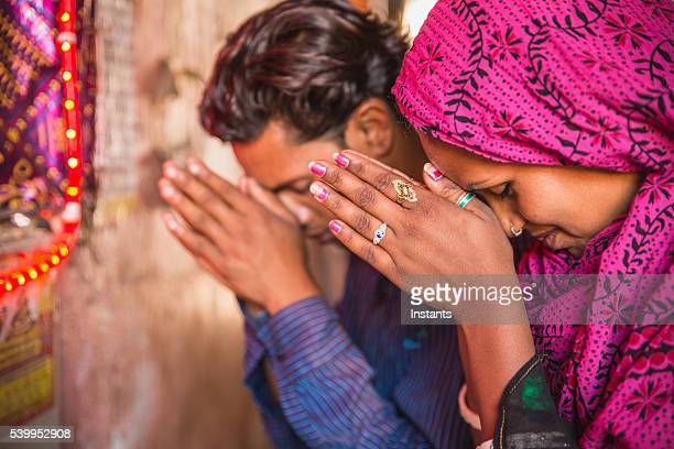 young indian couple praying - hinduism stock pictures, royalty-free photos & images