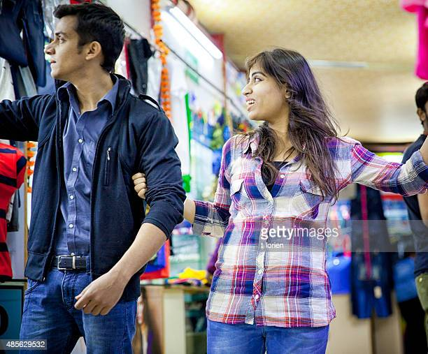 Young Indian Couple Shopping in opposite direction.