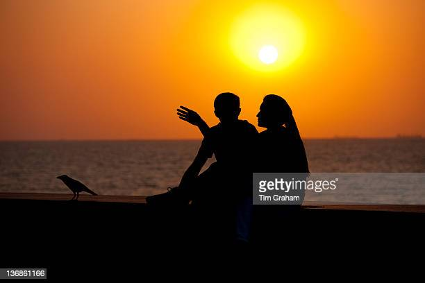 Young Indian couple sit on seawall at sunset at Nariman Point Mumbai formerly Bombay India