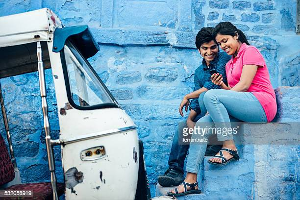 Joven pareja India usando teléfono inteligente en Jodhpur