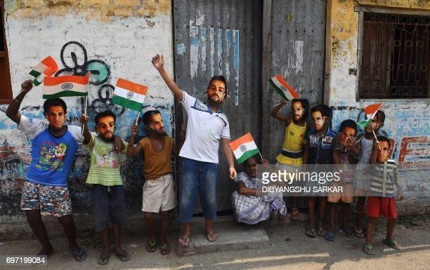 TOPSHOT Young Indian cricket fans wear masks of the face of India's captain Virat Kohli and others in Kolkata on June 18 to mark the Champions Trophy...