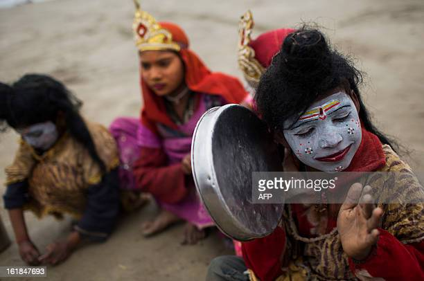 Young Indian devotees dressed as Gods play music and beg for food handouts at the Kumbh Mela in Allahabad on February 17 2013 The Kumbh Mela in the...