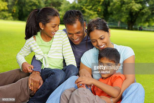 young Indian Family hugging and laughing together outdoors
