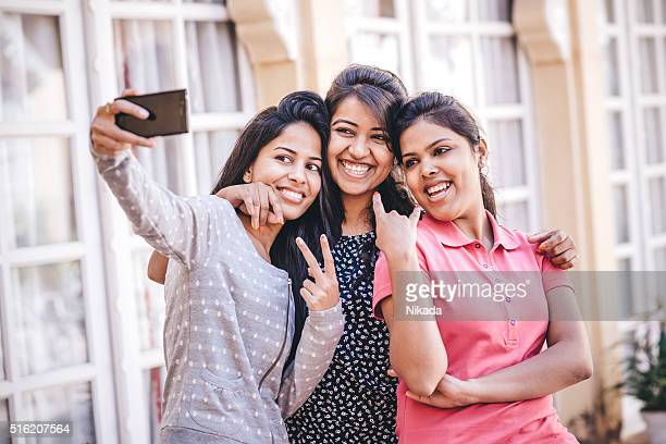 young indian female friends taking a selfie - images stock pictures, royalty-free photos & images