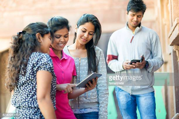 Young Indian friends using multiple devices
