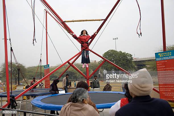 A young Indian girl bounces off a trampoline outside a Rajauri Gardens shopping mall in New Delhi India February 3 2008 India's middle class already...
