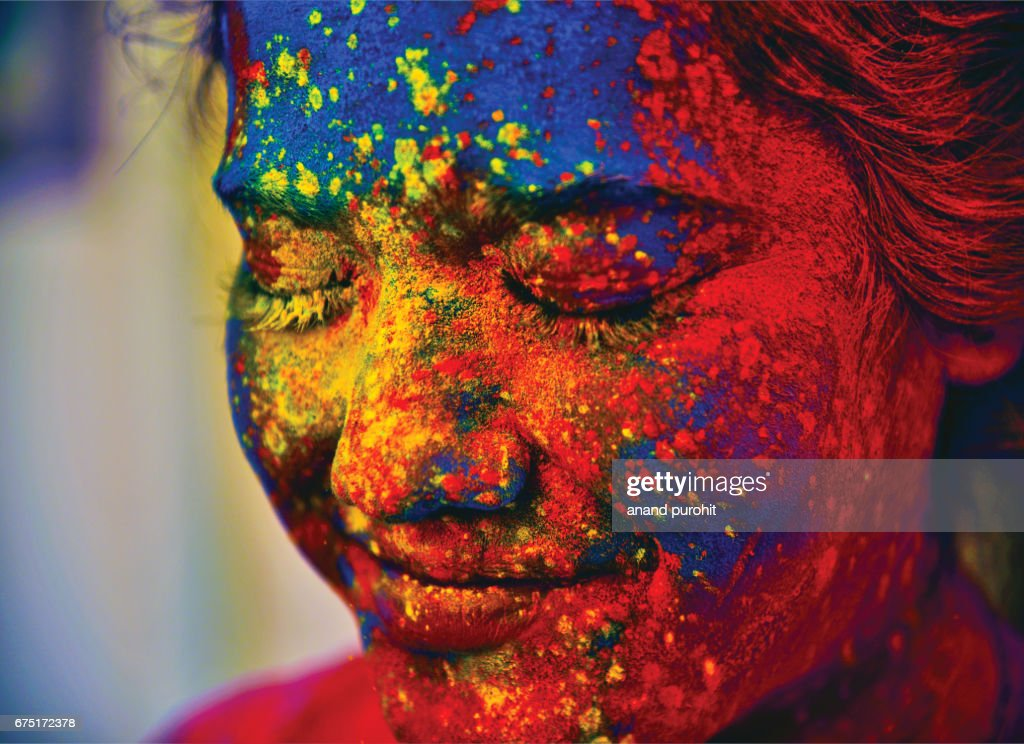 A young Indian girl, her face smeared with multicolored powder, during the Hindu festival of Holi, India : Stock-Foto