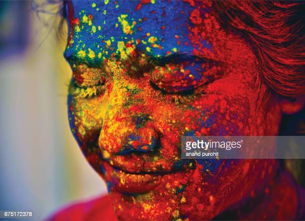 a young indian girl, her face smeared with multicolored powder, during the hindu festival of holi, india - cultures stock pictures, royalty-free photos & images