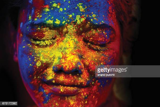 A young Indian girl, her face smeared with multicolored powder, during the Hindu festival of Holi, India