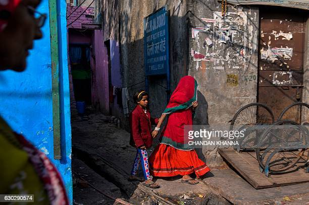 TOPSHOT A young Indian girl holds her mother's hand as she walks out of an alley in the Kathputli Colony in New Delhi on December 20 2016 The name...