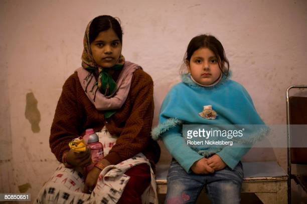 A young Indian girl right waits with her family's maid left outside a store in a New Delhi India market February 13 2008 With the nation's rapid...