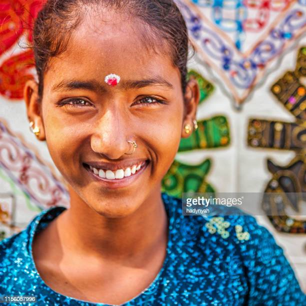 young indian girl selling colorful embroidered rugs - bindi stock pictures, royalty-free photos & images