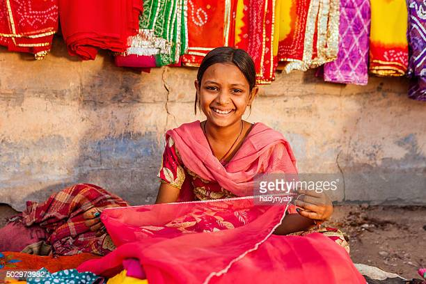 Young Indian girl selling colorful fabrics