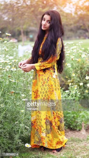 young indian girl standing in flowers - black hair stock pictures, royalty-free photos & images