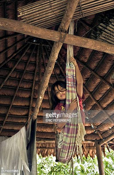 A young indian girl swings in her hammock inside the family hut 30 October 2004 on the banks of the Rio Apaporis in Colombia La Boudeuse a...