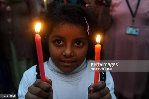 A young Indian girl with members of Akhil Bhartiya Human Rights organization holds lit candles at IndiaPakistan Wagah Border in India on December 10...