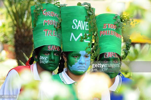 Young Indian girls pose with their painted faces during a 'Save Earth' awareness programme on the eve of World Earth Day at a school in Patiala on...