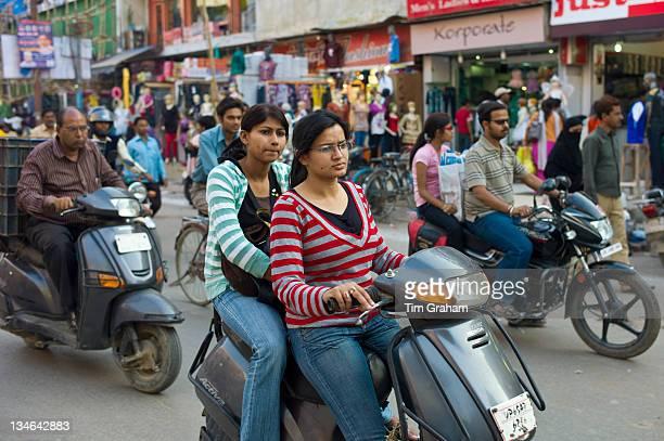 Young Indian girls ride motor scooter in street scene in city of Varanasi Benares Northern India