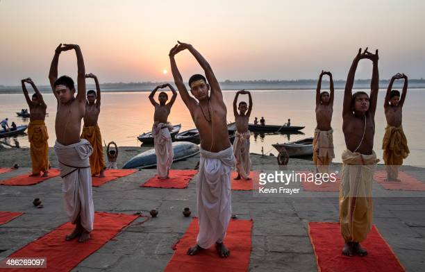Young Indian Hindu Brahmins training to be priests perform yoga on a ghat on the Ganges River holy to Hindus at sunrise on April 23 2014 in Varanasi...