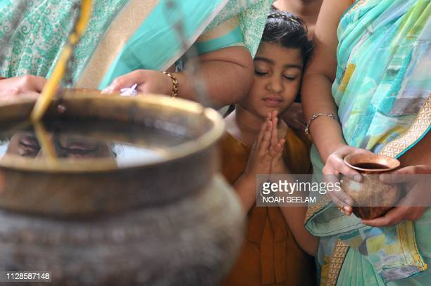 A young Indian Hindu devotee offers prayers to a Shiva Lingam a stone sculpture representing the phallus of the Hindu deity Shiva to mark the Maha...