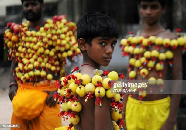 Young Indian Hindu devotees their bodies pierced with lemon and paladai bowl with a spout mainly used to feed milk to infants wait to participate in...