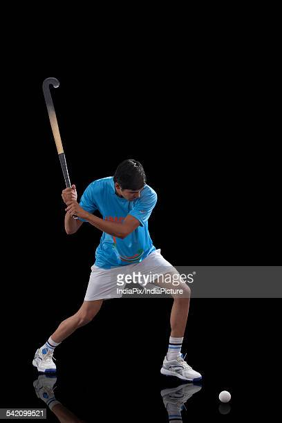 Young Indian hockey player about to hit a ball isolated over black background