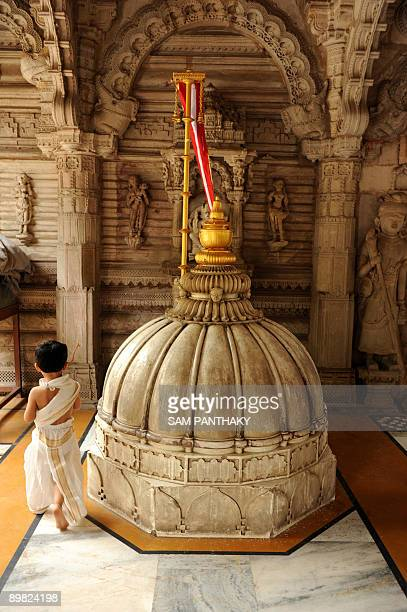 A young Indian Jain devotees wearing traditional clothes walks around a dome at the Hutheesing Jain temple in Ahmedabad on the occasion of the first...