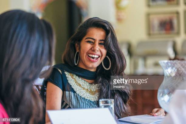 young indian man and two women spending some time together in a jodhpur restaurant. - traditional clothing stock pictures, royalty-free photos & images