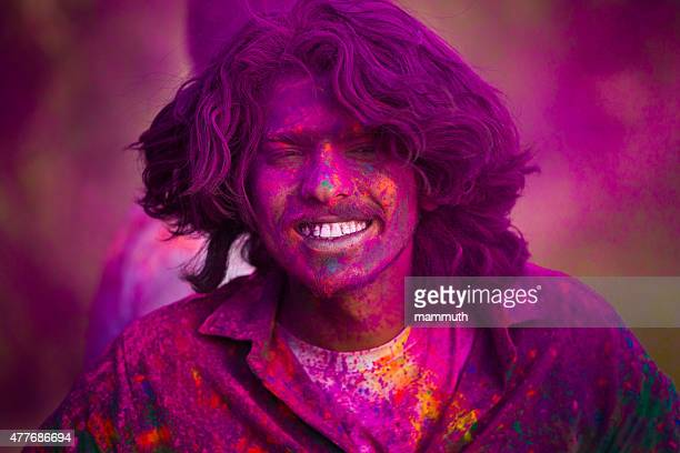 young indian man covered with colorful powders at holi festival