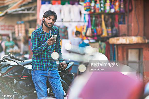Jeune indienne homme tenant le téléphone avec Pilote de moto