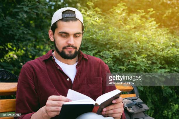 a young indian man sits on a bench in a public park with a book in his hands, on a sunny summer day against a background of green trees. a dark-skinned indian student in a cap reads, prepares for the exam and admission to an international university. - college admission stock pictures, royalty-free photos & images