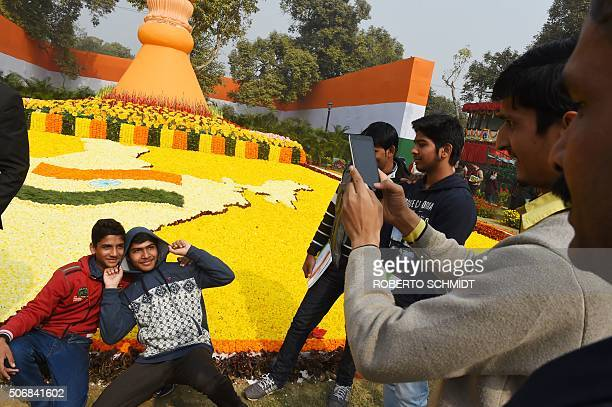Young Indian men pose for a photograph next to flower arrangements in the shape of the map of India at the end of India's Republic Day parade in New...