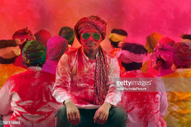 Young Indian Men sitting, covered in colored powder during holi color festival