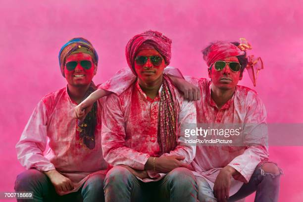 Young Indian Men sitting on bench, covered in colored powder during holi color festival