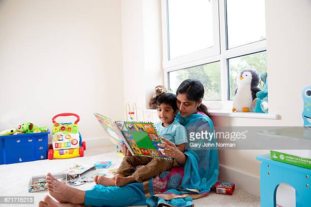 Young Indian mother reading with son at home