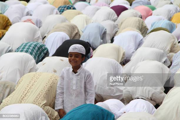 A young indian muslim boy looks on as others offer prayers on the last congregational friday of the holy month of Ramadan following the Muslim...