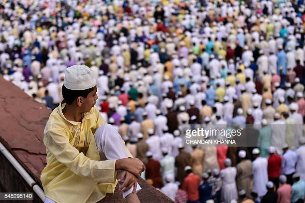 A young Indian Muslim boy looks on as people offer prayers during Eid alFitr at the Jama Masjid mosque in New Delhi on July 7 2016 The threeday...